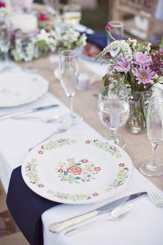 different china plates.    white tabel cloth burlap runner and blue napkins. nice look