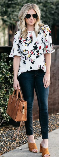 #spring #outfits woman wearing white, yellow, and blue floral quarter-sleeved shirt holding brown leather tote bag. Pic by @onesmallblonde