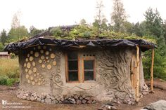 Natural Homes  This is Heidi's beautiful roundhouse in Finland [more pictures here www.naturalhomes.org/treeoflife.htm]. It has an earthbag stem wall with a birch bark damp proof membrane to protect the straw bale wall on the north side of the house and cob walls on stone on the south side. The green roof is supported by round timbers that interlock in a self supporting ring. It's known as a reciprocal roof [some examples here www.naturalhomes.org/fbr.reciprocalroofs].