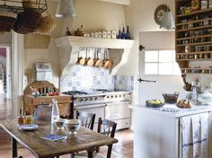 French style kitchen. Love the hanging pots and baskets, not to mention the blue tiling and rustic table. Very homey.