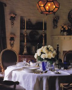 The setting of Craig Wright's dining room in his previous West Hollywood home is dripping with romance: a table straight from an Italian villa is elegantly set with starched linens, fine china, crystal and vermeil flatware before a fireplace set with vases of flowers and wall-mounted vases filled with roses flanking a niche holding elaborate Italian candlesticks. From Los Angeles: A Certain Style by Pilar Viladas. Photo by John Vaughan.