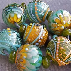 Beautiful set of SEVEN rounds in blue, light turquoise, green, yellow and white. There are also accent lines in peach yellow and spots in coral. Lots of fine detail. | Artist: Magdalena Ruiz, Las Palmas, canary islands, Spain | magdalenaruiz on etsy | mrumruglass on Flickr