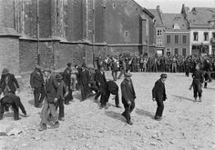 The city of Doesburg, the Netherlands. Collaborators cleaning the streets. A large crowd is watching them.