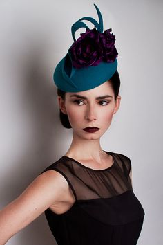 TIGER LILY £325.00  Handcrafted in our London studio.  Peachbloom felt cocktail hat with feather and handmade silk flowers.  Colours: Teal, Purple.  Secured with a comb and elastic.  1 in stock.  UK delivery 3-5 working days.  Sent free within the UK. Includes a Black & White striped hatbox.
