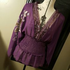 NWT Incredibly sexy Rampage purple top This is a very sexy dark purple Rampage top, a little bit see through. would be perfect with a black cami, incredible butterfly sleeves with right sleeve sequenced flower design, and around the neck into a V is a lace sequins design, with a elastic design waist. Never worn with tags Rampage Tops Blouses