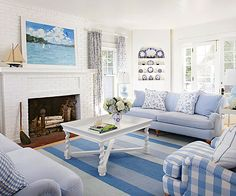 In this sunny living room, a white and blue scheme lays a foundation for cottage style. A white brick fireplace and corner built-in hutch bring architectural detail to the space. French doors let in light and open up to the b/ Blue Living Room Decor, Cottage Living Rooms, Small Living Rooms, Coastal Living, Cozy Living, Cottage Style Decor, Cottage Style Homes, French Country Living Room, French Cottage