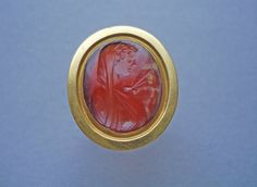 Intaglio; sard; bust of Psyche to left, mantle thrown over head; butterfly alighted on throat; in plain gold ring; inscribed.