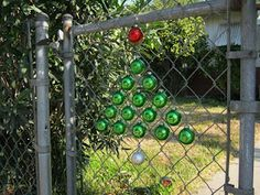 Decorated chain link fence with hanging Christmas ornaments. (But the hanging decorations could be anything small.)