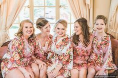 Bridal party wearing floral robes sitting on pink couch, bridal party robe ideas