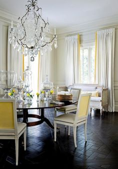 Yellow and gray dining room with soft gray paneled walls, white curtains with canary yellow ribbon trim, dark wood…