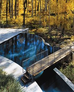 Blending in with the neighboring woodland, this vanishing-edge pool appears to flow endlessly into its surroundings. The bridge overlooking the pool provides the ideal spot to enjoy the natural beauty and the pool's sophisticated allure.