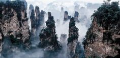 """Tianzi Mountain, China  The most charming view of the """"stone towers"""" covered with thick clouds can be perceived from Tianzi Mountain of China. Only a handful of people visit this place every year because it is very difficult and risky to climb. But the place is worth the risk and difficulty."""