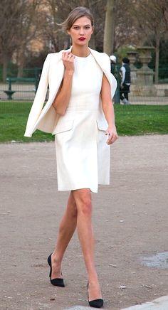 White blazer slung over shoulders, white dress, and black heels