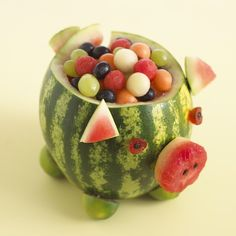 PIG WATERMELON  This is a fun way to serve fruit for a party and it's always greeted with squeals of delight.. Cut out the snout and ears from the top of the watermelon and cut out a spiral tail at the back.  Use a melon baller to make balls of watermelon and then scoop out the remaining flesh. Fill with balls of watermelon, cantaloupe and honeydew melon  and some black and white grapes. Make eyes from glacé cherries and raisins and feet from limes.