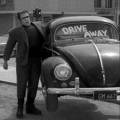 Herman Munster lifts a VW Beetle. The shadow of the arm lifting the car can be seen on the bottom-right of the photo.