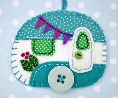 Vintage caravan trailer hanging ornament, handmade from felt and decorated with fabric scraps. With tiny felt bunting and buttons for the wheel and door knob. Colours are teal and white. With blanket