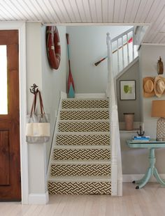 coastal beach style entry with light blue-green tinted white walls, geometric feature on staircase, turquoise side table, coastal accessories