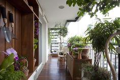 Varanda com piso de cumaru, vasos de plantas, cadeiras de madeira, e lanternas da L'Oeil. Projeto de paisagismo na varanda de um apartamento, feito pela paisagista Claudia Muñoz, da Línea Paisagismo