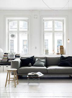 grey sofa + white wood floors + exposed diamond bulb + bare windows