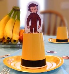 Curious George Place Settings. Put a yellow cup on a yellow plate, and wrap some black electrical tape around the cup to make a yellow hat