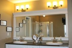 "I SO want to do this in all of our bathrooms, ""frame"" the builder grade mirrors."