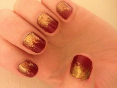 Red nails with gold sparkle on bottom.