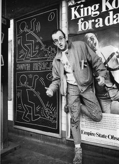 Keith Haring standing beside one of his subway drawings (Keith Haring artwork, Keith Haring Foundation).