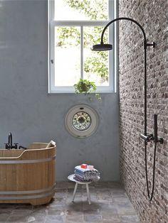 bañera de madera y ducha abierta en pared de ladrillo visto