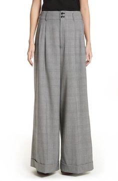 A voluminous wide-leg cut offers easy swing to smart pleated trousers tailored in rich plaid wool.