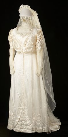 "Wedding Dress: Made 1915, Modified 1945. ""Jeanette Gunn modified her mother's 1915 wedding gown for her own wedding to Doug Motter in 1945. A professional seamstress removed the original high neckline and its net and lace inserts, replacing it with a sweetheart neckline, popular in the 1940s. The original silk satin dress was made in London Ontario by Smallman and Ingram Limited for Anna Martin's Calgary wedding to Dr. John Gunn..."""