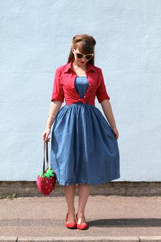 Collectif strawberry bag, red and white polka dot tie shirt and sunglasses with a 50s style denim sundress