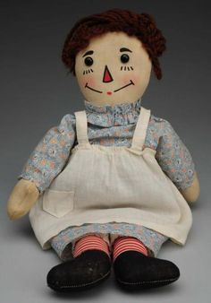 Late 1920s. All cloth with printed features, rosy cheeks, brown yarn hair, wooden heart