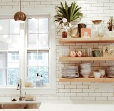 Kitchen with floating shelves near sink
