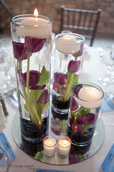 Absolutely elegant Valentine flower centerpiece display. Easy to replicate - tall clear glass vases, roses, stones for the bottom (amethyst would be gorgeous) and floating candles.