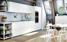 Cocina blanca con encimeras en gris claro; acabada con un horno microondas, un horno y un extractor de acero inoxidable.