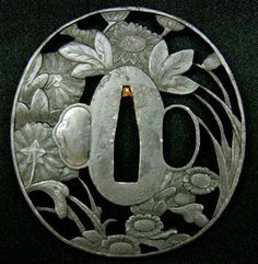 Tsuba, a Japanese sword guard, typically elaborately decorated and made of iron or leather