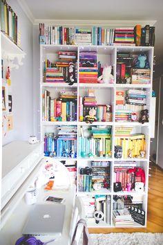 Estante de livros cheia de livros no quarto da Melina Souza. Parte da estante é organizada por cor.
