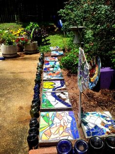 recycled garden in progress -wine bottle edge,  mosaic river and other mosaics on found objects