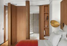 Una delle camere da letto dell'Hotel Vernet di Parigi, con pannelli in legno e lampada da comodino in lastre di ottone