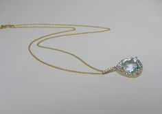 """Pear shaped aquamarine drop set in a diamond halo of 18K gold. 18"""" necklace"""