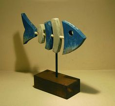 Figure of fish in wood and metal. Blue, grey and wood at the base. Black metal support. Size of the figure 25 cm high, 10 cm. wide and 23 cm. long approximately. Hand-made craft product. Each piece is different and may not match exactly with the photographs.