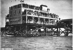 Refreshment rooms at the end of Henley Beach jetty. 1918. Crowds packing the verandahs and roof-top areas of refreshment rooms at the end of the jetty at Henley Beach. Swimmers are sitting on the structure below and other spectators are standing on the jetty. By State Library of South Australia : http://images.slsa.sa.gov.au