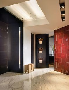 """A custom-designed, red-glass wall treatment greets guests as they enter the foyer, where small stools from Andiamo A Casa emphasize the scale of this apartment. """"Originally I was going to use red marble on these walls. But when I saw it was more terra cotta, I created the glass wall instead,"""" Calderin says. """"Most of the pieces are frosted; very few are glossy."""""""