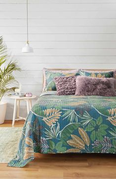 Faded floral patterns add vintage tropical style to a crisp quilt that reverses to a painterly geo pattern.