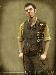 modern cloathing accessorized with steampunk odds and ends to fit the genre as an airship captain. waistcoat, pocketwatch, goggles, utility belt shoulder strapped, keys, maps, pilot pin