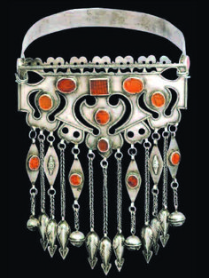 Silver and carnelian Bukov of a more unusual style, having simple silver graphically cut out designs set with carnelian on an egraved strap. Probably Ersari late  19th c