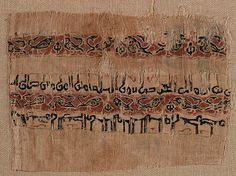 996-1021, Egypt. Tiraz fragment with birds. Linen tabby with silk tapestry. Pairs of confronted birds occupy the decorative band between two kufic inscriptions that name the Fatimid Caliph al-Hakim (ruled 996-1021).
