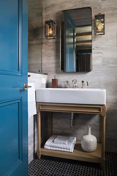 A cerulean blue door opens to a bathroom filled with faux bois tiled walls lined with a curved metal shelf mirror illuminated by galvanized metal wall sconces situated over a Restoration Hardware Weathered Oak Single Console Washstand placed atop a black hexagon tiled floor.
