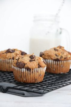 Chunky Monkey Muffins on a cooling rack with milk in the background