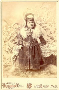 A beautifully - and warmly - attired young Victorian girl posing for a portrait in her winter finery
